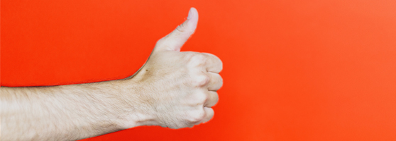 forearm extending from the left of frame to give a thumbs up on an orange background